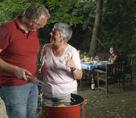 Bbq in the garden with man and woman on foreground