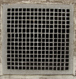 irregular metal grid from a ventilation shaft in a concrete wall poster