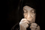 Old Woman Deep in Prayer wearing a black Veil