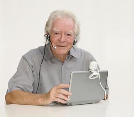 Älterer Herr mit Netbook, Webcam und Headset