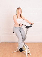 Young blonde woman on her exercise bike
