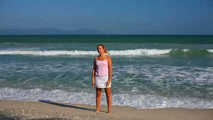 young woman doing morning exercises on the beach