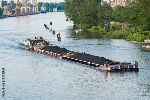 Leinwanddruck Bild coal barge sailing on the river