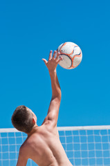 young boy playing volleyball on beach