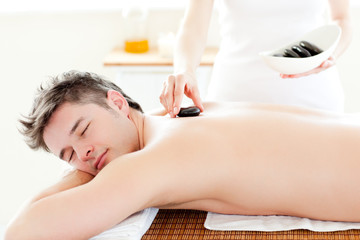 Charming young man receiving a massage with hot stone