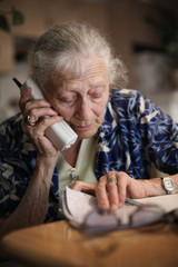 Senior woman talking on the phone at home