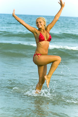 Beautiful young woman jumping on a beach.