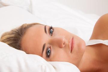 Frau liegt wach im Bett. Schlaflos und nachdenklich.