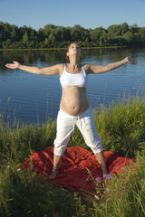 Pregnant woman exercising on the river bank