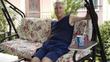 Old retired man on porch swing - Retirement Home poster