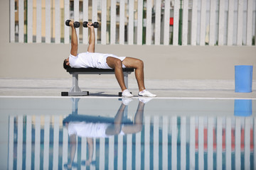 young man exercise at poolside