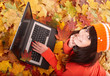Girl in autumn orange leaves with laptop.