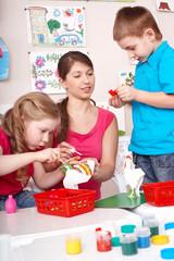 Children painting with teacher.