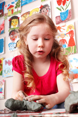 Child girl play clay in play room.