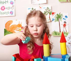 Child preschooler play wood block.
