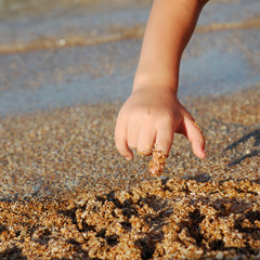child drawing on sand