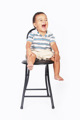 Excited baby sitting on black chair isolated