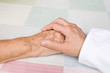 hand of a doctor holding the hand of an elderly patient
