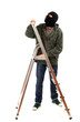 thief in black balaclava with ladder