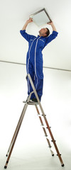 young man on ladder attaching lamp