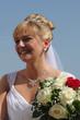 Schöne junge Braut mit Hochsteckfrisur vor blauem Himmel