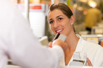 Kassiererin im Supermarkt nimmt Kreditkarte