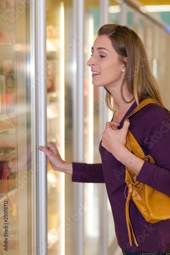 Woman in supermarket freezer section