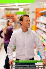 Mann und Frau im Supermarkt mit Einkaufswagen