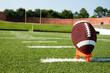 Closeup of American Football on Tee on Field