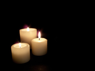 Close up of three lit candles on black background.