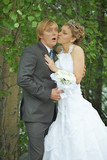 Amusing groom and bride kiss secretly