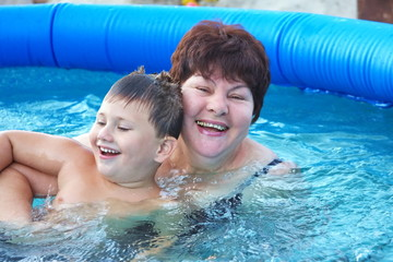 grandmother with a grandchild in a pool