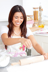 Lively asian woman baking in the kitchen