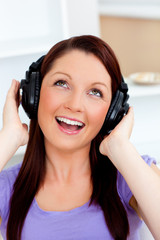 Singing young woman listening to music