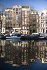 Dutch houses in Amsterdam reflected in a channel