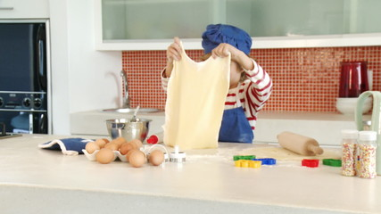 young boy making a dough in his kitchen
