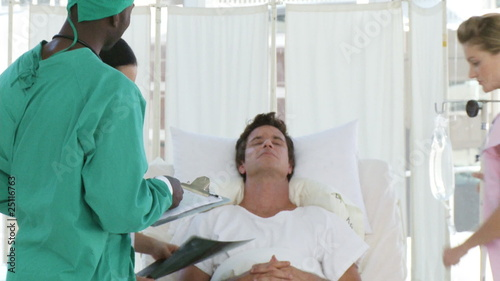 Clinic team around a patient lying on a bed