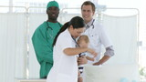 female doctor looking after little boy with two doctors behind