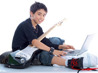 smiling boy with guitar & notebook computer isolated on white