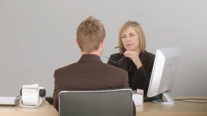 Two associates talking at a desk