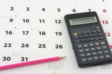 Calculator and pencil on the calendar