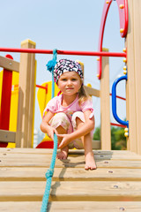 Pretty little girl on playground equipment