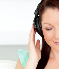 Delighted woman listening to music with headphones at home