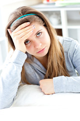 Depressed young woman sitting in the kitchen
