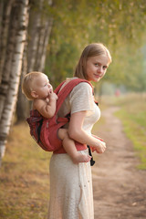 mother and daughter walking near forest by the road