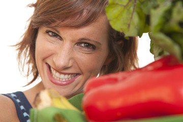 Close up portrait of young woman smiling with vegetables