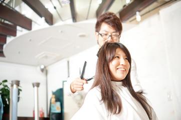 女性の髪を切る男性美容師