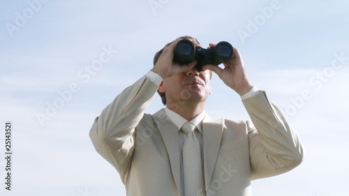Businessman outside watching via binoculars