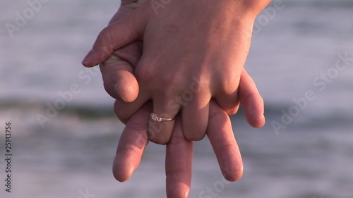 close up of a couple holding hands in front of the sea
