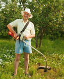 man works with cordless grass trimmer poster